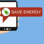 """A hand holding a smartphone with a dialog box saying """"Save Energy""""."""